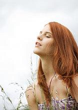 Rothaarige junge Frau im Gras