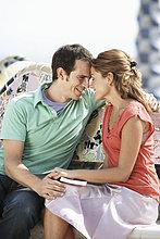 Paar sitzend Angesicht zu Angesicht mit Stirn berühren, lächelnd, Nahaufnahme