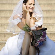 Eine Braut sitzend außerhalb der Kirche