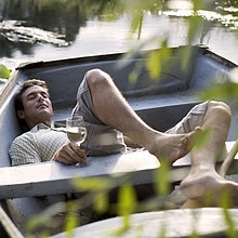 Junger Mann in einem Boot trinken Wein Verlegung