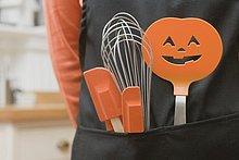 Küchenwerkzeuge für Halloween stecken in einer Schürze
