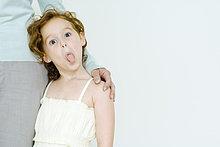Little Mädchen hält auf Mutter Bein, Zunge herausstrecken, in die Kamera