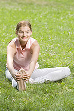 Portrait of young Frau macht stretching Übung im park