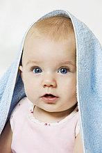Nahaufnahme eines cute Baby Mädchen mit blauen Handtuch über Kopf