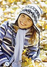 Mütze mit Strickmütze liegt im Herbstlaub