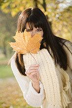 hinter ,Portrait ,Frau ,verstecken ,Pflanzenblatt, Pflanzenblätter, Blatt ,braunhaarig ,Herbst