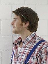 Mann in Arbeitskleidung und Bleistift hinter dem Ohr