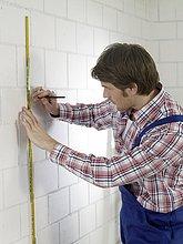 Mann in Arbeitskleidung mit Bleistift und Zollstock