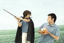 Vater und Sohn spielen, Mann, hält jack o ' Lantern, Boy Schwert schwingen