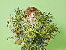 Junge versteckt sich hinter grünen bush