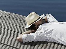 Ein junger Mann liegend auf einer Mole