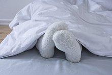 Detail Frau liegend im Bett, die Füße in Wollsocken