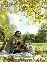 Seitenansicht reife Frau hält Scheibe Brot und lächelnd in Park