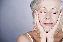 ältere Frau mit Kopf Ausruhen im Hände