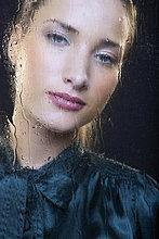 Frau am Regen überdachten Fenster