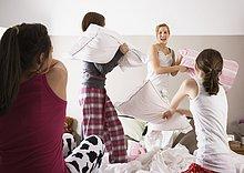 Mädchen mit Kissen kämpfen auf Slumber party