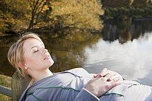 Frau liegt auf Zaun an einem See