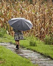Junges Mädchen spaziert im Regen in Nepal