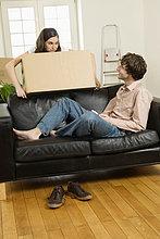 Junges Paar beim Umzug, Mann liegt auf Sofa, Frau trägt Karton