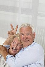 Ausgelassenes Seniorenpaar auf der Couch