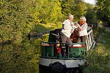 Paar stößt an Weingläser auf Boot im Kanal