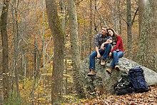 Junges paar sitzen auf Boulder in Gesamtstruktur