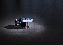 Student schläft auf Schreibtisch in dunklem Raum