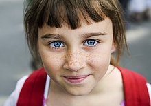 Portrait of a girl with big blue eyes and freckles, Sweden.