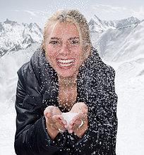 Junge Frau lächelt mit Schnee