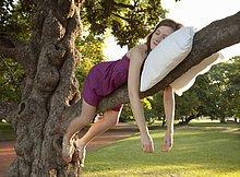 Junge Frau schlafen auf einem Baum