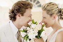 Brautpaar riecht an Brautstrauß