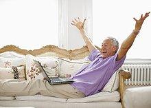 Jubelnder Mann auf dem Sofa mit Laptop