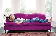 Mann schläft auf lilafarbenem Sofa