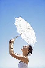 Braut Sonnenschirm gegen blauen Himmel hält