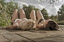 Zwei junge Frauen liegen auf einem Holzsteg und sonnen sich