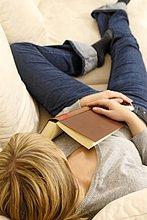 Junge Frau liegt auf dem Sofa