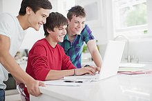 Smiling teenage boys using laptop together