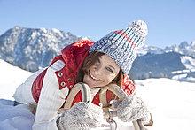 Lächelnde Frau liegt auf einem Schlitten, Tannheimer Tal, Tirol, Österreich