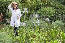 Portrait of a Seniorin hält Blumen in einem Garten