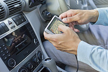 Nahaufnahme der menschlichen Hand mit GPS Navigations-System im Auto