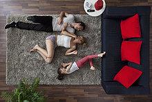 Eine Familie von drei glücklich liegen auf einem Wohnzimmer Teppich, Drachen