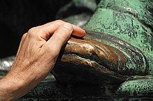 Hand auf dem blanken, bronzenen Schuh des Denkmals von Johann Wolfgang von Goethe, gilt als glücksbringend, Ecke Opernring Goethestraße, Wien, Österreich, Europa