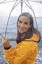 Junge Frau am Strand mit Regenschirm