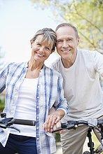 Lächelndes Seniorenpaar mit Fahrrädern