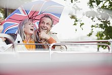 Glückliches Paar mit Regenschirm in einem Doppeldeckerbus