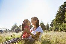 Mutter und Tochter reiben ihre Nasen auf einem sonnigen Feld
