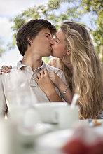 Junges Paar küsst sich im Freien am Gartentisch