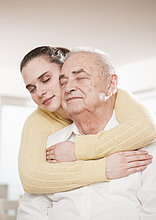 Young woman hugging senior man