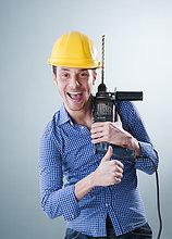 Fröhlicher junger Mann mit Bauhelm hält eine Bohrmaschine