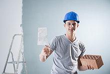 Junger Mann mit Bauhelm hält Maurerkelle und Ziegelstein